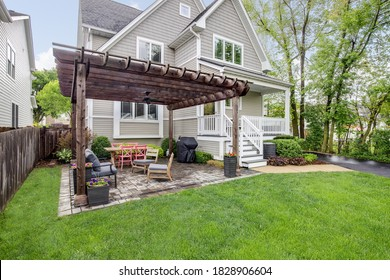 ELMHURST, IL, USA - MAY 22, 2019:  A backyard brick patio with lots of seating, a grill, and a wooden pergola over the top of a luxurious home.