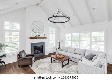 ELMHURST, IL, USA - MAY 26, 2020: A modern farmhouse living room with shiplap, exposed white beams, a fireplace, and furniture on hardwood floors.
