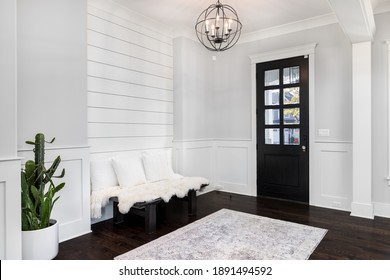 ELMHURST, IL, USA - NOVEMBER 1, 2020:  A beautiful foyer entrance with a light hanging above the dark hardwood floors, a bench in front of a shiplap wall, and a dark door with windows.