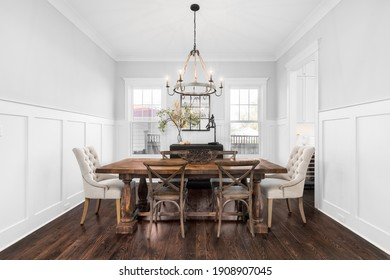 ELMHURST, IL, USA - NOVEMBER 4, 2020 - A modern dining room with rustic, farmhouse decor. A large wood table and chairs sit below an iron and rope chandelier.