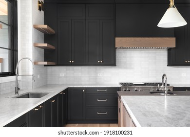 ELMHURST, IL, USA - OCTOBER 2, 2020: A luxury kitchen with black cabinets, granite counter top, tiled backsplash, stainless steel appliances, and chrome faucets.