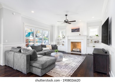 ELMHURST, IL, USA - OCTOBER 26, 2020: A cozy, white living room with a large grey sectional couch, an area rug on hardwood floors, and a white fireplace with built-in shelves.
