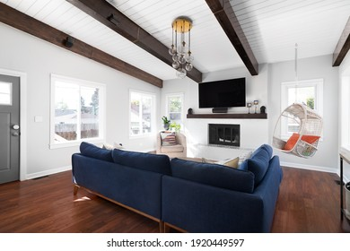 ELMHURST, IL, USA - SEPTEMBER 2, 2020: A renovated modern farmhouse living room with a blue couch, white fireplace, wood beams on a white shiplap ceiling, and a television mounted above the fireplace.