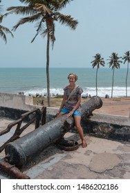 Elmina / Ghana - 03.14.2015: A photo of a European woman posing on a huge cannon at Elmina castle. Ocean can be seen on the background.