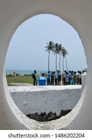Elmina / Ghana - 03.14.2015: A view to the beach thorough the window of the St George of the Mine. Gathering ghanaian crowd on the background of palm trees can be seen.