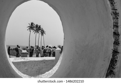 Elmina / Ghana - 03.14.2015: A view to the beach thorough the window of the St George of the Mine. Gathering crowd on the background of palm trees can be seen. Black and white.