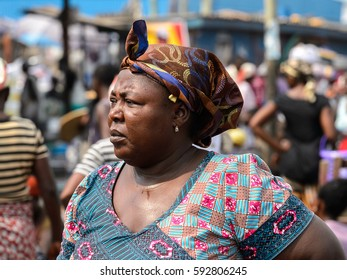 ELMINA, GHANA -JAN 18, 2017: Unidentified  Ghanaian woman in colored dress and headscarf looks ahead in Elmina. People of Ghana suffer of poverty due to the bad economy