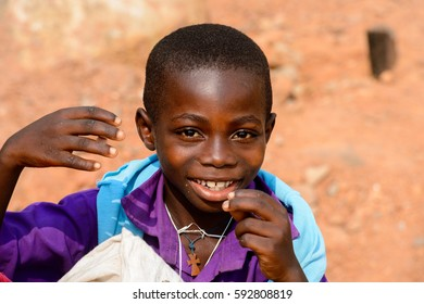 ELMINA, GHANA -JAN 18, 2017: Unidentified  Ghanaian little boy in purple shirt smiles in Elmina. Children of Ghana suffer of poverty due to the bad economy