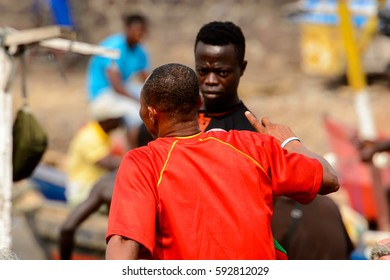 ELMINA, GHANA -JAN 18, 2017: Unidentified  Ghanaian men from behind on the shore of Elmina port. People of Ghana suffer of poverty due to the bad economy