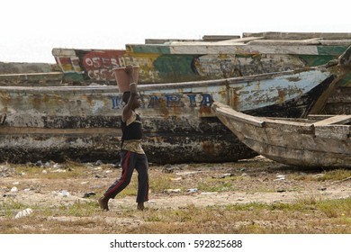 ELMINA, GHANA -JAN 18, 2017: Unidentified  Ghanaian boy carries a bucket on his head on the coast of Elmina. People of Ghana suffer of poverty due to the bad economy