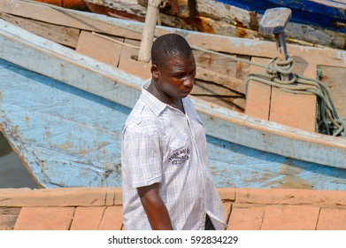 ELMINA, GHANA -JAN 18, 2017: Unidentified  Ghanaian man walks along the road in Elmina port. People of Ghana suffer of poverty due to the bad economy.