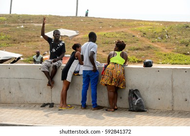 ELMINA, GHANA -JAN 18, 2017: Unidentified  Ghanaian people stand near the fence on the coast of Elmina. People of Ghana suffer of poverty due to the bad economy
