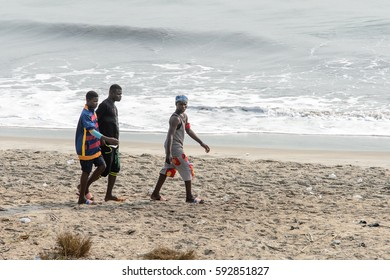 ELMINA, GHANA -JAN 18, 2017: Unidentified  Ghanaian young boys in colored clothes hang out on the coast of Elmina. People of Ghana suffer poverty due to the bad economy