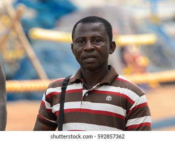ELMINA, GHANA -JAN 18, 2017: Unidentified  Ghanaian man in striped shirt walks in Elmina port. People of Ghana suffer poverty due to the bad economy