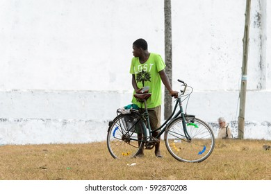 ELMINA, GHANA -JAN 18, 2017: Unidentified  Ghanaian man pulls his bicycle on the coast of Elmina. People of Ghana suffer of poverty due to the bad economy