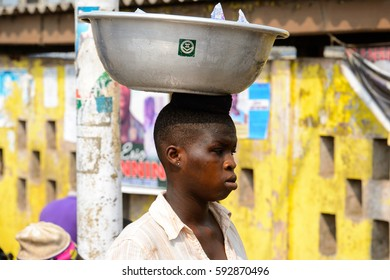 ELMINA, GHANA -JAN 18, 2017: Unidentified  Ghanaian woman carries a basin on her head in Elmina market. People of Ghana suffer of poverty due to the bad economy