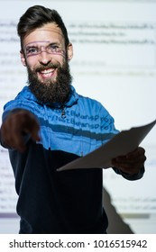 Elocution or speech craft courses. Bearded young male orator smiling and interacting with someone in the audience pointing a finger. Dialogue, discussion and rhetoric basics concept