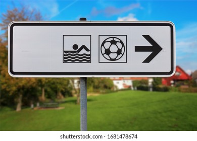 An elongated black and white sign shows the way to a soccer field or stadium and to an indoor swimming pool in Germany. In the background a lawn, trees and a blue sky.