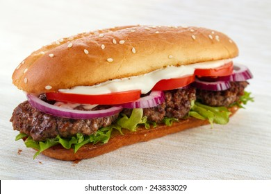 Elongated hamburger (burger sandwich) with three grilled patties , lettuce ,  red onion , tomato and mayonnaise