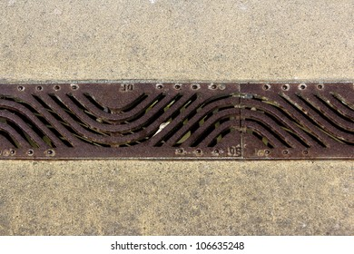 A elongated stylized floor drain made out of cast iron on the ground with patterns