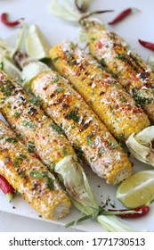 Elotes, grilled Mexican street Corn, Summer, BBQ , fast, healthy food concept, top view, flat lay, white background, decorated with red hot chili peppers lime and cilantro leaves