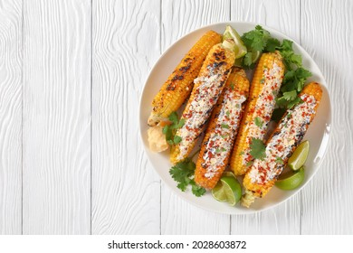 Elotes, Grilled Mexican Street Corn, charred cobs are covered in creamy mayonnaise, seasoned with chili powder and sprinkled with cheese, cilantro, and a spritz of lime juice, flat lay, free space