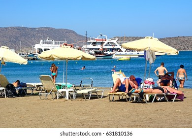 ELOUNDA, CRETE - SEPTEMBER 17, 2016 - Tourists relaxing on the beach, Elounda, Crete, Greece, Europe, September 17, 2016.