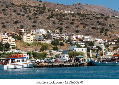 Elounda, Crete/Greece - August 15, 2018: View over small town of Elounda in the eatern part of Crete island, Greece. Small portfrom where boats go to Spinalonga. Houses in the hill.