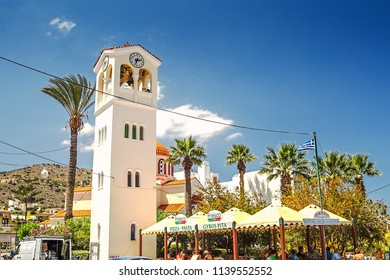 Elounda, Greece, Crete - 05/24/2015: Clock tower with a Greek church to the rear in the town centre