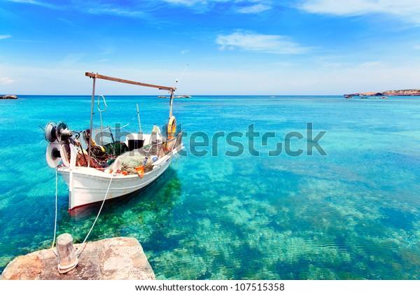 Els Pujols Strand in Formentera mit traditionellem Fischerboot im Sommer