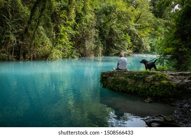 ELSA RIVER, ITALY - SEPTEMBER 15, 2019: one unknown woman with dog at Elsa river park, the trail starts in Gracciano and reaches in Colle Val d'Elsa (Siena, Tuscany) the river's waters are turquoise