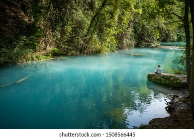 ELSA RIVER, ITALY - SEPTEMBER 15, 2019: one unknown woman at Elsa river park, the trail starts in Gracciano and reaches in Colle Val d'Elsa (Siena, Tuscany) the river's waters are  turquoise color