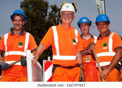 """Elsfleth, Germany - August 29, 2018: Stephan Weil, Prime Minister of Lower Saxony together with three workers of the construciton company """"Joachim Tiesler KG"""", all dressed in orange working suit"""