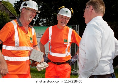 Elsfleth, Germany - August 29, 2018: Stephan Weil, Prime Minister of Lower Saxony in orange safety working suit and helmet tagether with an other worker talks to a man in white shirt