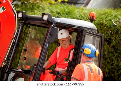 Elsfleth, Germany - August 29, 2018: Stephan Weil, Prime Minister of Lower Saxony, sits in orange working dress and white helmet in an excavator in a construction zone and is instructed by a worker