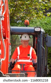 Elsfleth, Germany - August 29, 2018: Stephan Weil, Prime Minister of Lower Saxony, sits in orange working dress and white helmet in an excavator in a construction zone - frontal view
