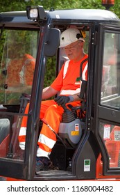 Elsfleth, Germany - August 29, 2018: Stephan Weil, Prime Minister of Lower Saxony, sits in orange working dress and white helmet in an excavator in a construction zone - side view