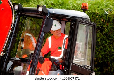Elsfleth, Germany - August 29, 2018: Stephan Weil, Prime Minister of Lower Saxony, sits in orange working dress and white helmet in an excavator in a construction zone and looks around the corner