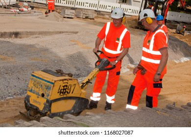 Elsfleth, Germany - August 29, 2018: Stephan Weil, Prime Minister of Lower Saxony, in orange working dress and white helmet with a heavy machine in a construction zone beeing instructed by a worker