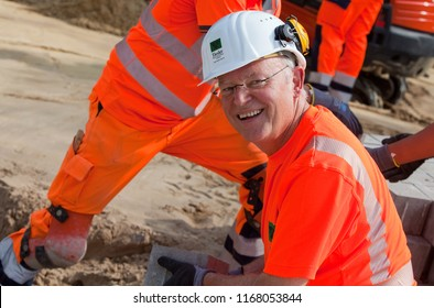 Elsfleth, Germany - August 29, 2018: Stephan Weil, Prime Minister of Lower Saxony, sits in orange working dress and white helmet in a construction zone for road works