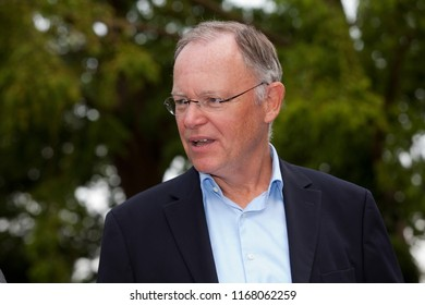 Elsfleth, Germany - August 29, 2018: outdoor portrait of Stephan Weil, Prime Minister of Lower Saxony in front of dark green background