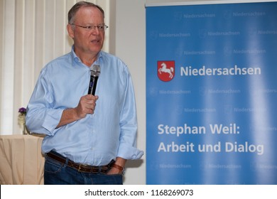"""Elsfleth, Germany - August 29, 2018: Stephan Weil, Prime Minister of Lower Saxony next to a blue banner with the word """"Niedersachsen"""", his name and the name of the event he is talking at"""