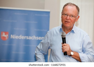 """Elsfleth, Germany - August 29, 2018: Stephan Weil, Prime Minister of Lower Saxony in front of blue banner with the word """"Niedersachsen"""" and the coat of arms speaks via microphone to a public audience"""