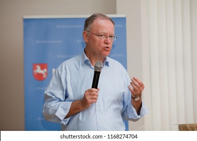 Elsfleth, Germany - August 29, 2018: Stephan Weil, Prime Minister of Lower Saxony in front of a blue banner speaks via microphone to a public audience and uses body language to explain his position