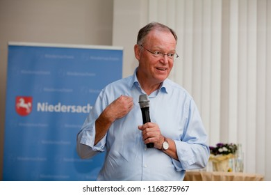 Elsfleth, Germany - August 29, 2018: Stephan Weil, Prime Minister of Lower Saxony in front of a blue banner speaks  to a public audience and points to himself to explain his position
