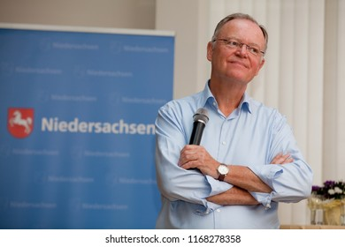 Elsfleth, Germany - August 29, 2018: Stephan Weil, Prime Minister of Lower Saxony stands with crossed arms in front of a blue banner and has a significant face