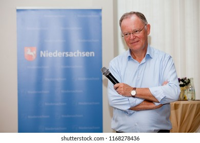 Elsfleth, Germany - August 29, 2018: Stephan Weil, Prime Minister of Lower Saxony stands with crossed arms in front of a blue banner and smiles satisfied