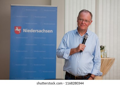 Elsfleth, Germany - August 29, 2018: Stephan Weil, Prime Minister of Lower Saxony stands with microphone in one hand and one in the pocket in next to a blue banner and lookes satisfied and attentive