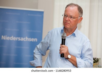 Elsfleth, Germany - August 29, 2018: Stephan Weil, Prime Minister of Lower Saxony with microphone next to a blue banner, he listens attentively