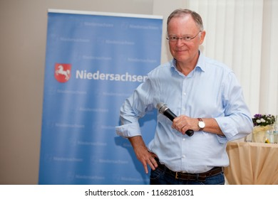 Elsfleth, Germany - August 29, 2018: Stephan Weil, Prime Minister of Lower Saxony stands with hand on the hip in front of a blue banner and smiles satisfied